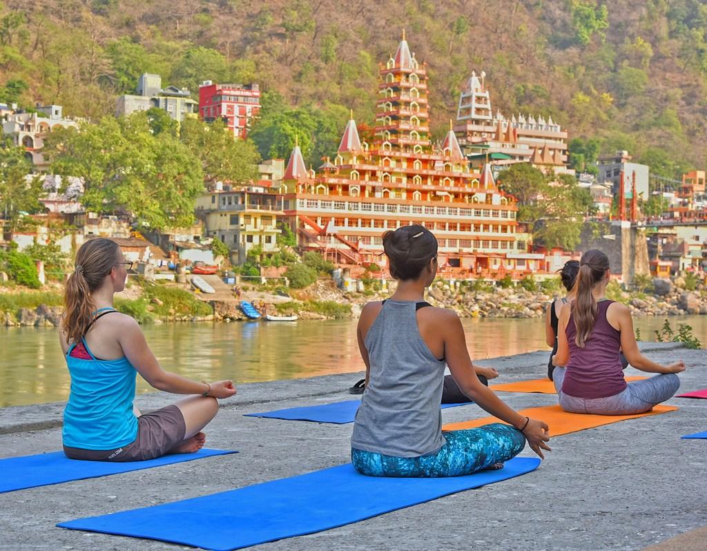 people doing yoga besides Ganga river in Rishikesh
