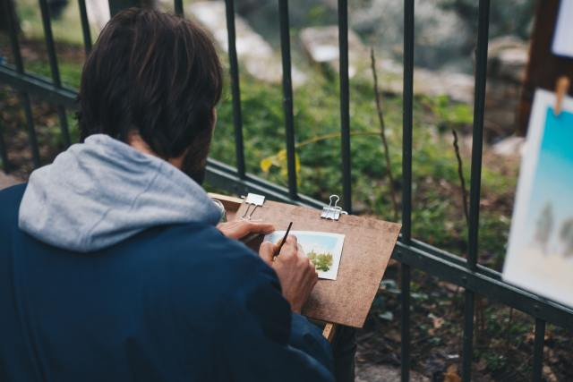 man sitting and drawing