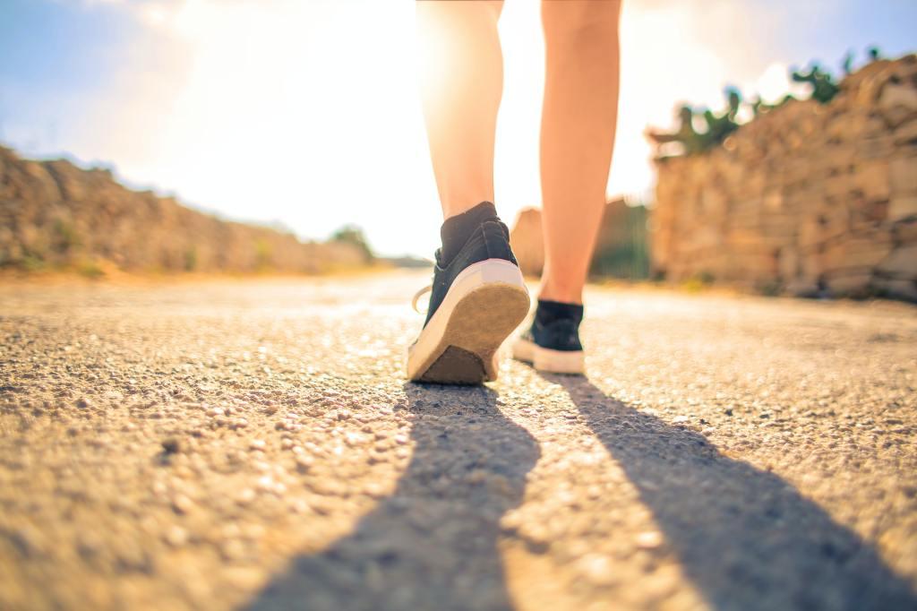 Woman Walking on Pathway Under The Sun